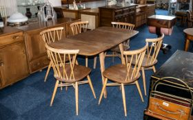 An Ercol Drop Leaf Dining Table, of typical form, together with six dining chairs.