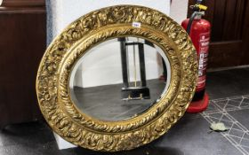 """A Circular Bevelled Glass Gilt Framed Mirror with embossed scroll and shell decoration. 26"""" x 30""""."""