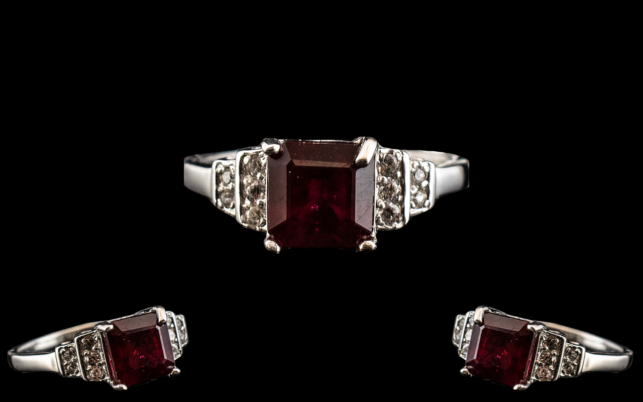 Ruby and Zircon Ring, a square cut, 2.5ct ruby solitaire set to the centre, flanked by round cuts of