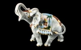 Porcelain Figure of an Elephant with trunk raised, and decorative gilt and coloured highlights on