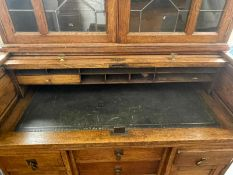 A Small Golden Oak Tambour Fronted Fitted Roll Top Desk, with a matching leaded glass cupboard top,