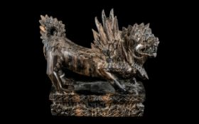 A Carved Wooden Griffin, raised on a rectangular carved plinth in Oriental style. Height 8.