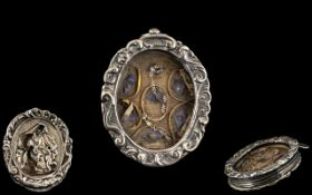 An Italian Silver Relic housed in an oval frame, glazed front,