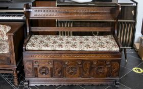 Mid 20th Century Monks Bench of typical form with hinged seat and carved panelled front,