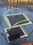 Chrome Art Deco Style Drinks Trolley, atomic shape on caster feet, with two mirrored glass shelves.