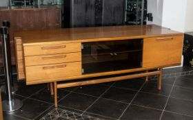 A Mid Century Designer Teak Sideboard, with a glass centre covered doors,
