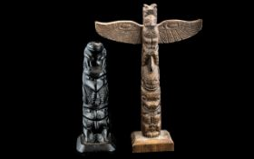 Two North American Indian Totems, depicting winged birds and masks, with a frog perched on the top.