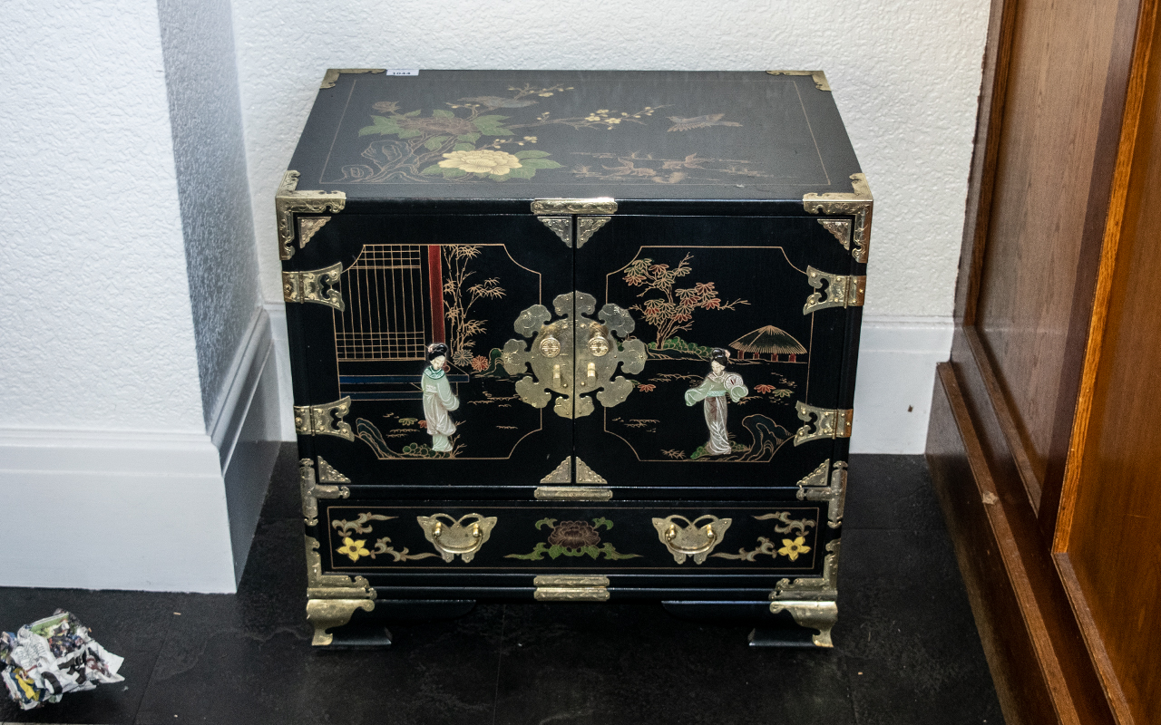 A Chinese Black Lacquered Cabinet, painted floral gilt decoration in enamels, with two door front