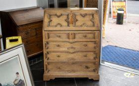 A Modern Light Oak Bureau, fall front above four graduating drawers in a Jacobean style.