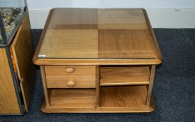 An Ercol Coffee Table, square form, with shelves and drawers, raised on casters, with glass top.