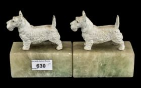Pair of Art Deco Cold Painted Metal Highland Terrier Book Ends, raised on marble bases.