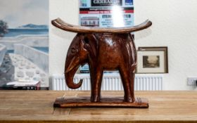 """An African Style Elephant Stool in hardwood, varnished. Measures 18"""" high x 20"""" length x 10"""" width."""