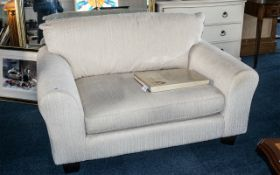 Two Seater Contemporary Overstuffed Sofa, covered in an ivory coloured material, on square feet.