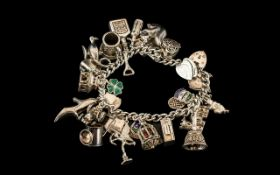 A Vintage Sterling Silver Charm Bracelet Loaded with 25 Silver Charms.