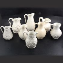 Eight assorted Victorian Parian relief-moulded jugs