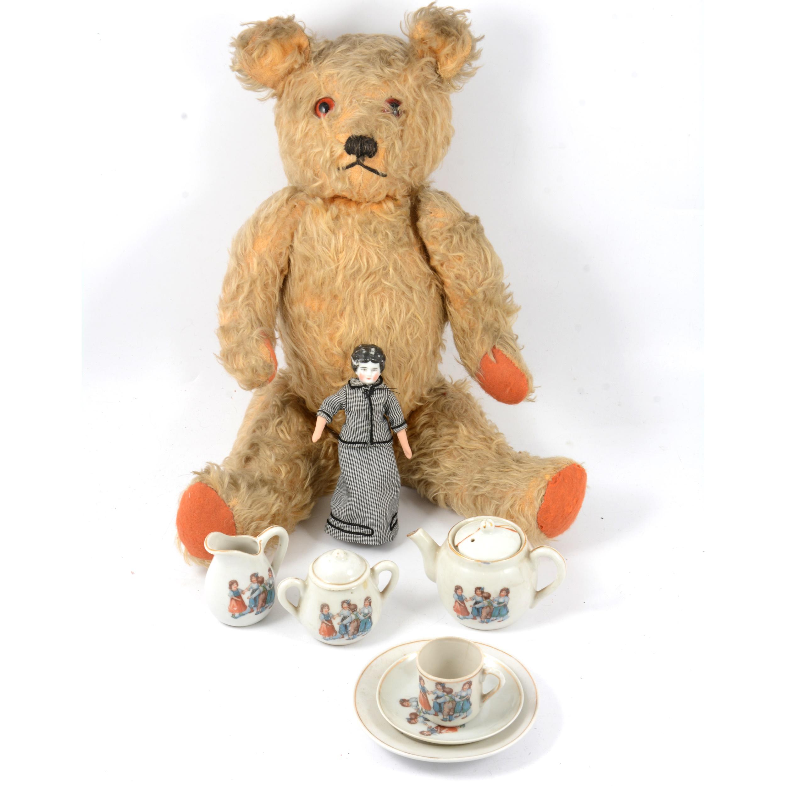 A mid-20th century mohair teddy bear, miniature doll and tea set.