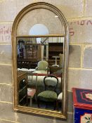 A modern gilt framed wall mirror, the arched top with an inset lacework panel, width 59cm, height