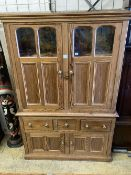 An early 19th century stripped pine cupboard, fitted with a pair of part glazed panelled doors, over