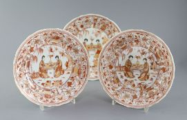 A set of three Chinese rouge de fer moulded dishes, Kangxi period, each painted with two ladies