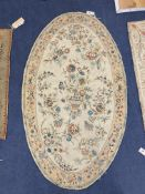 An Antique oval chain-stitch panel centred with flowers in a basket on a cream ground, 151 x 88cm