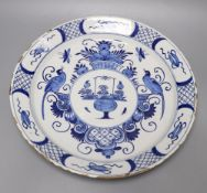An 18th century blue and white Delft charger, 35cmCONDITION: Shallow chips and flakes to rim, no