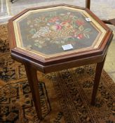 An grois point tapestry panel, inset in the top of a hexagonal mahogany table, width 54cm, depth