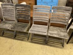 A set of four weathered teak folding garden chairs
