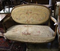 A Louis XVI style carved walnut (?) canape with Aubusson-style upholstery, length 144cm, 104cm high