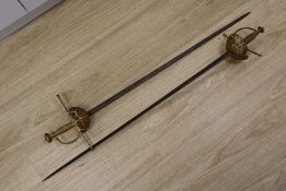 A pair of duelling swords, with cast hilts and 35 inch blades