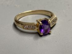 A modern yellow metal, amethyst ring with white stone (possibly white sapphire) set shoulders,