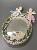 A 19th century Meissen porcelain framed oval mirror surmounted with two angelic figures, height