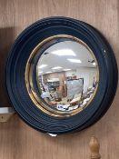 An ebonised framed convex mirror, with a gilt slip