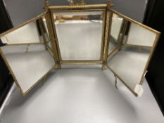 A gilt framed triptych mirror with faux ivory angelic panel and similar floral painted panel, height