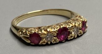 An 18ct Victorian style two stone diamond and three stone ruby set half hoop ring, size K/L. gross