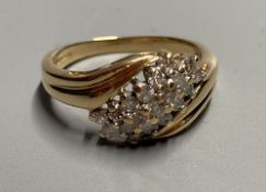 A modern 18ct gold and nineteen stone three stone three row diamond crossover ring, size N, gross