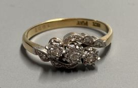 An 18ct and plat. illusion set three stone diamond crossover ring, size O/P, gross 3 grams.
