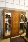 An Edwardian satinwood banded and inlaid mahogany triple wardrobe with fitted interior, width 175cm,