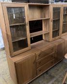An Ercol elm glazed bookcase, width 155cm depth 44cm height 162cm