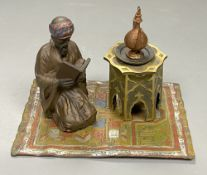 A cold painted bronze desk stand modelled as a reading Arab, length 14.5cm
