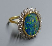 An 18ct, black opal doublet and diamond set oval cluster ring, size M, gross 7.3 grams.CONDITION: