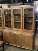 An Ercol display cabinet fitted three glazed panelled doors over cupboards, width 136cm depth 44cm