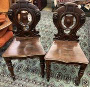 A pair of Victorian mahogany hall chairs