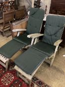 A pair of weathered teak steamer garden chairs with cushions