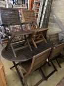 A weathered teak garden table and six teak folding chairs (two with arms)