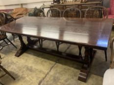 An 18th century style oak refectory table having planked top on double turned end supports, width