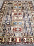 An Afghan Kazak blue, red and ivory ground rug with all-over stylised motifs, 294 x 216cm