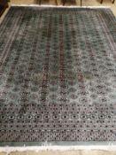 A Pakistan Bokhara green ground carpet, 350 x 282cm