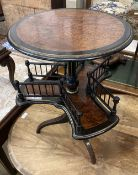 A Victorian ebonised and gilt thuya book table, the circular top over revolving trefoil book rack