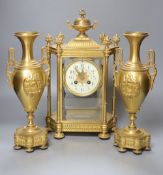 A late 19th century French garniture de cheminée comprising a four-glass mantel clock and a pair