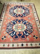 A peach ground rug centred by two stylised foliate blue ground medallions, 230 x 170cm
